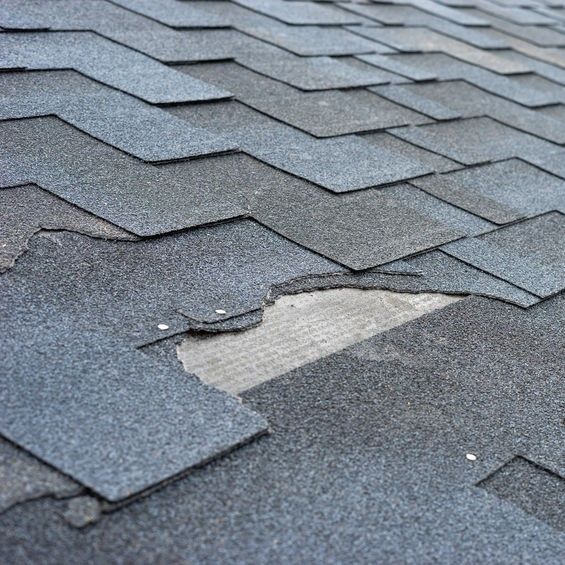 damaged shingle roof with cracked materials