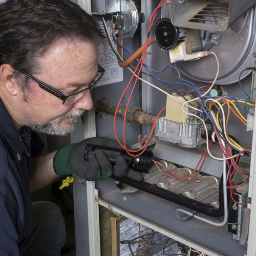 Technician Instigating Furnace Repair